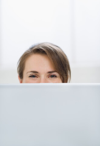 Woman Hiding Behind Laptop Screen