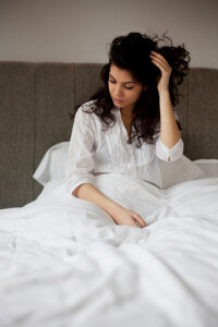 Woman Sitting Up In Bed Looking Worried